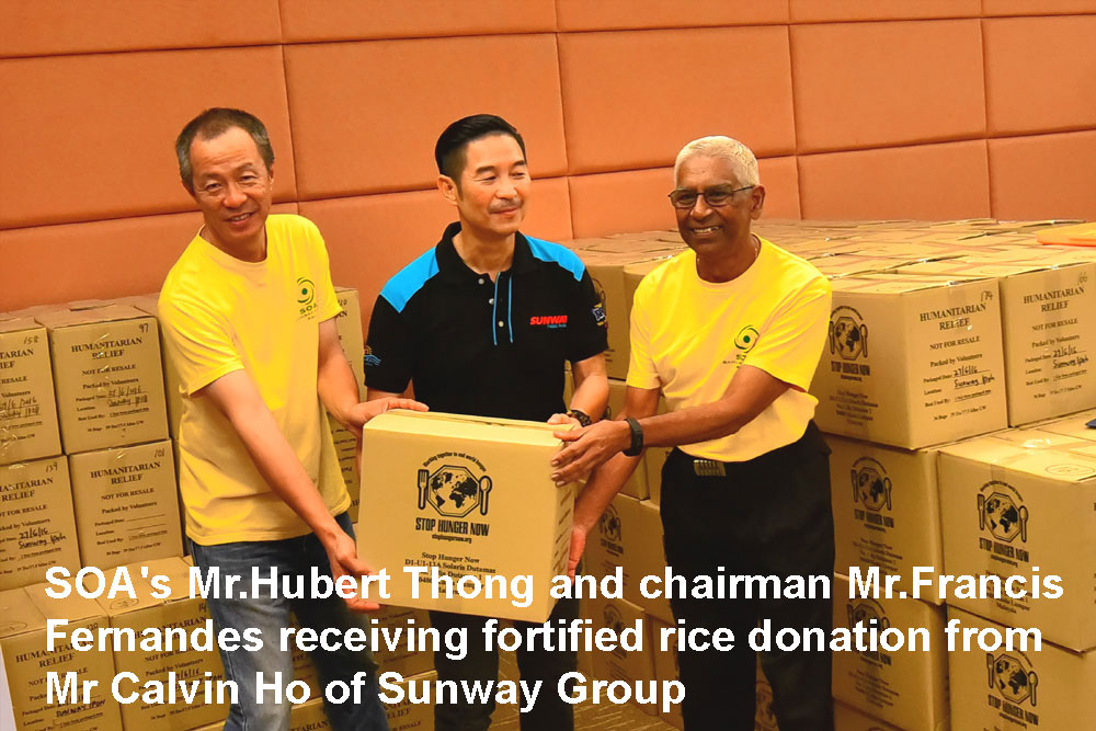 Hubert Thong and Francis Fernandes receive rice packs from Sunway's Calvin Ho