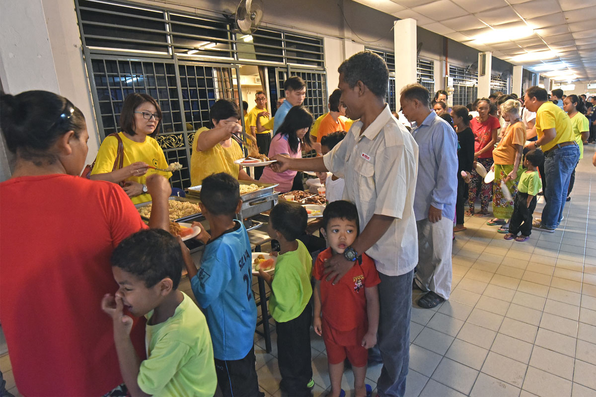 SOA members and Chinese Apostolate serve dinner to orang asli at parish hall