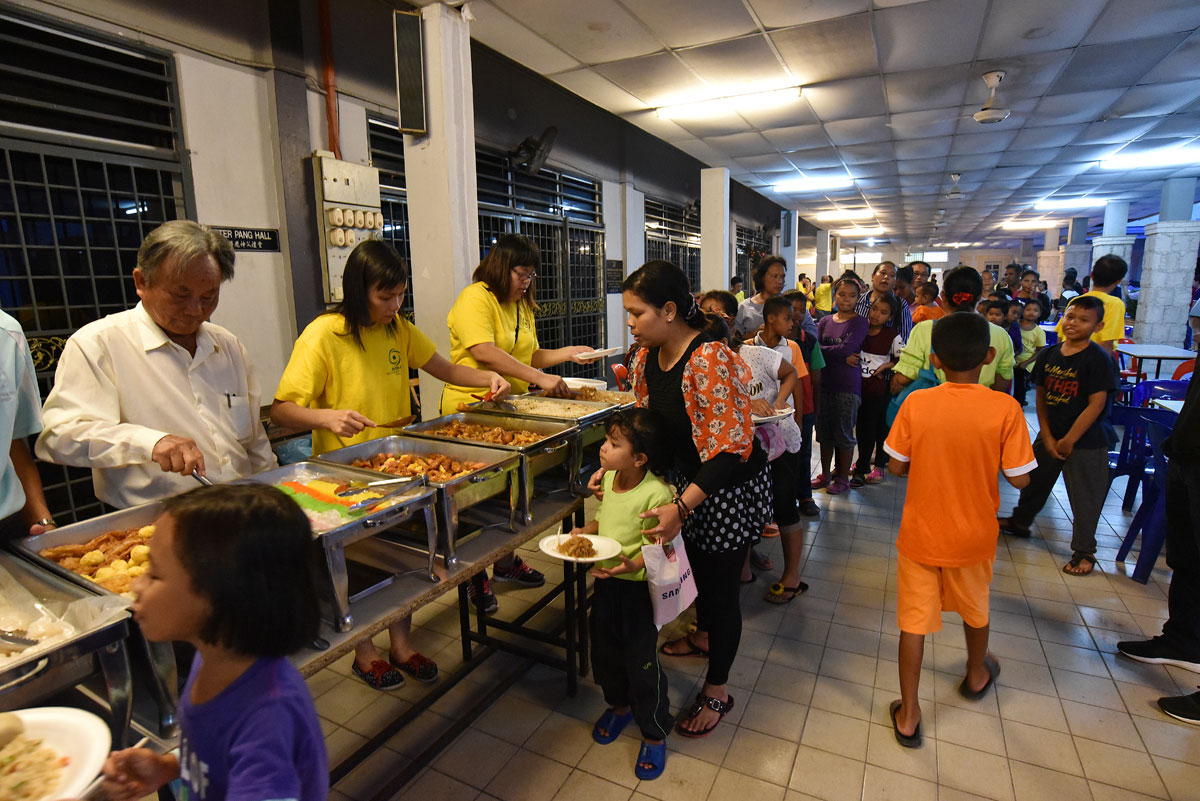 Chinese Apostolate and SOA members serve dinner to orang asli at parish hall