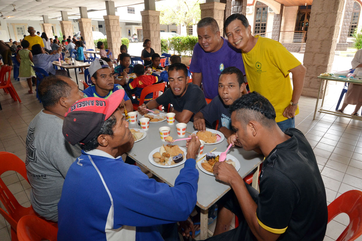 SOA members serve lunch to orang asli at parish hall